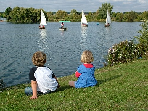 two young children watch boats go by